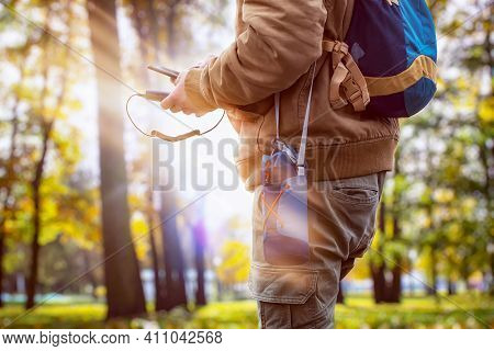 Man Hiker In The Forest Is Charging A Smartphone With A Portable Charger. Power Bank In A Man's Hand