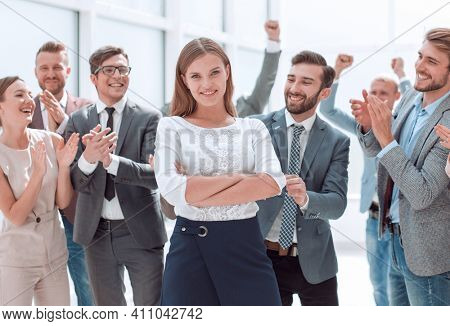 confident team leader standing in front of her colleagues
