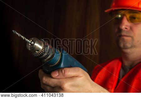 Woodworker Holds An Electric Drill Close-up During Carpentry Work. Working Environment In A Carpentr