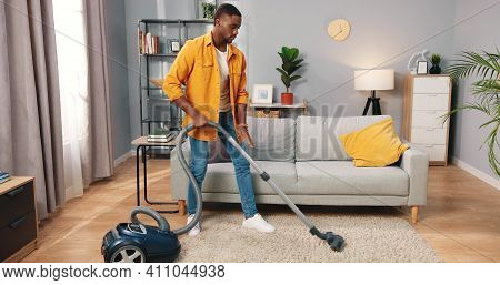 Handsome African American Young Concentrated Busy Man Vacuuming Cleaning Modern Living Room, Male Wo