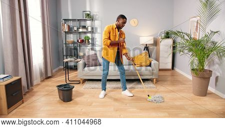 African American Busy Handsome Young Guy Washing Floor In Modern Living Room Doing Housework, Male C