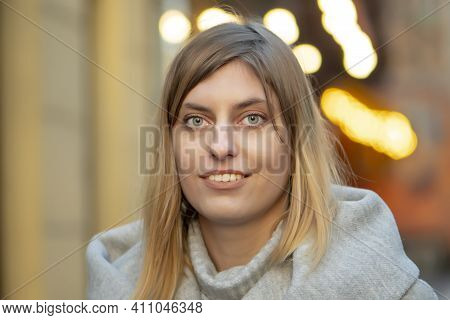 Cute White Young Woman 25-30 Years Old With Blonde Hair On A Blurry Urban Background.