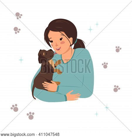 A Woman Holds A Labrador Retriever Puppy In Her Arms. The Dog Licks The Owner On The Cheek. Happy Pe