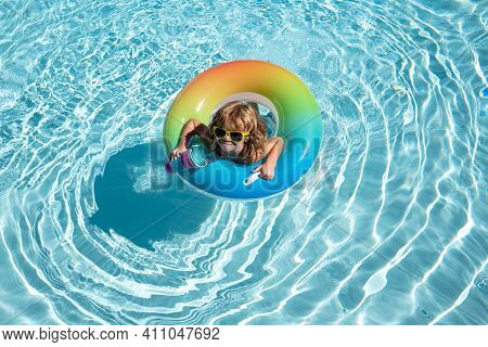 Summer Kid Swim At Swimming Pool. Funny Happy Child Boy In Swiming Pool On Inflatable Rubber Circle