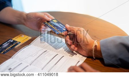 The Bank Clerk Is Presenting The Benefit Of The Credit Card To A Customer Who Applied For A Credit C