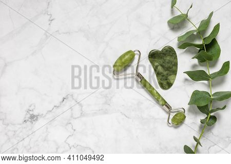 Green Jade Roller And Gua Sha Stone For Facial Massage And Eucalyptus Branch On Marble Background. H