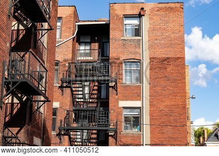 Rear View Of An Old Apartment Building With Black Steel Fire Escapes And Balconies, Horizontal Aspec