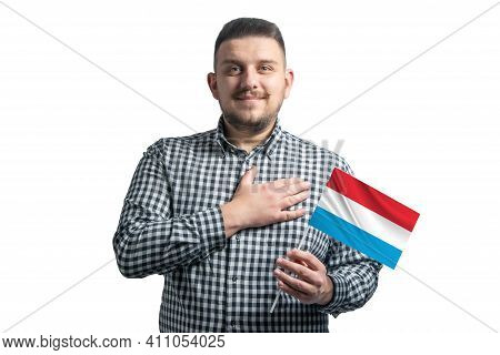 White Guy Holding A Flag Of Luxembourg And Holds His Hand On His Heart Isolated On A White Backgroun