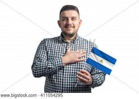 White Guy Holding A Flag Of Nicaragua And Holds His Hand On His Heart Isolated On A White Background