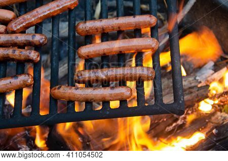 Roasting hotdog over open flame campfire. Grilling delicious meat hot dog over fire pit. Camping and