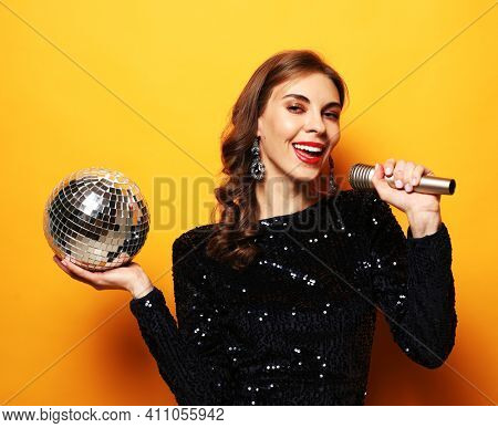 Party, holiday and celebration concept:Elegance brunette woman with long curly hair dressed in evening dress holding disco ball and microphone, singing and smiling over yellow background