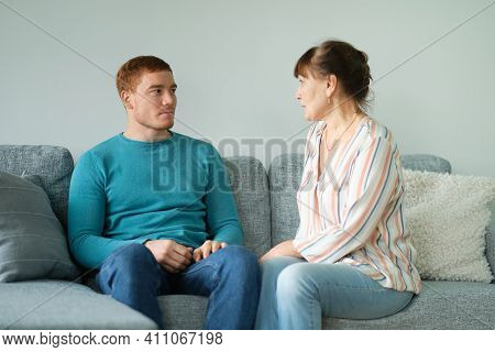 Elderly Mother Tells Her Son Her News. Cheerful Elderly Woman Sitting On The Sofa Next To His Adult