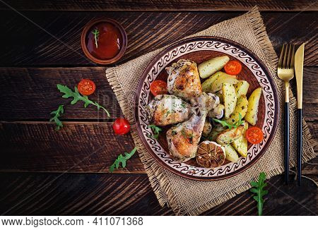 Baked Chicken Legs With Slice Potatoes And Herbs. Barbecue Chicken Drumsticks On Wooden Table. Top V