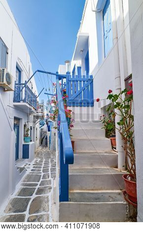 Romantic Traditional Narrow Cobbled Streets Of Greek Island Towns. Whitewashed Houses, Flower Pots,
