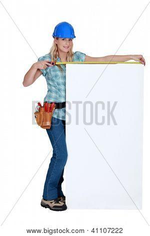 Tradeswoman measuring a blank sign