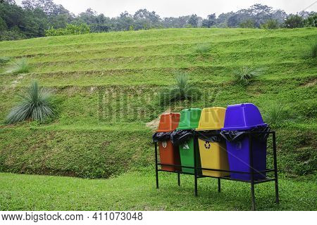 Colorful Bin Over Green Filed, Conservative Environment Concept, Separate Type Of Gabage With Multi