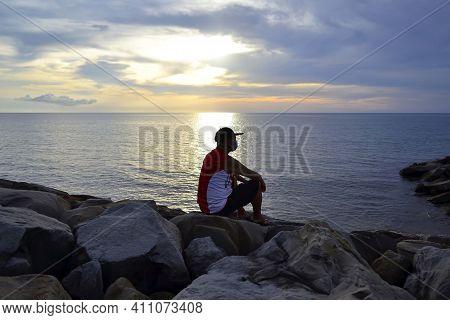 Man Wearing Facemask Sitting On A Rock Watching The Sunset At Sea In Tanjung Aru Kota Kinabalu Beach