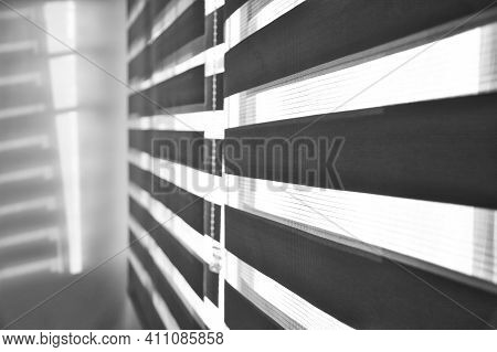 Sun Shining Through Window Blinds Throwing Shadows On The Wall In Black And White