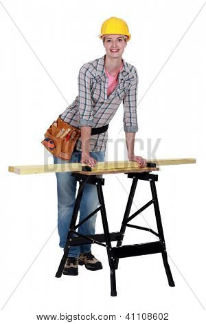Tradeswoman leaning against a workbench