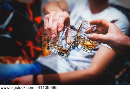 Glass With An Alcoholic Drink, Against The Background Of Bottles With Alcohol. Alcohol Addiction. Ha