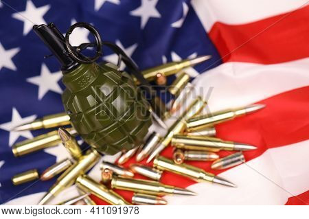 F1 Frag Grenade And Many Yellow Bullets And Cartridges On United States Flag. Concept Of Gun Traffic