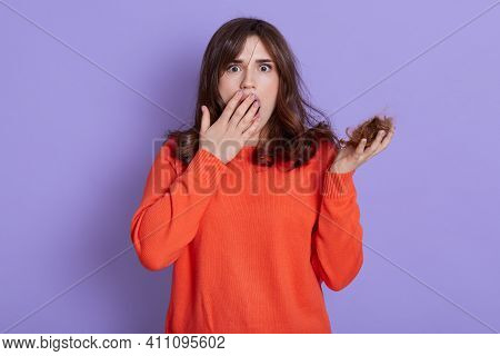 Beautiful European Woman Holding Loosing Hair, Looks Scared And Amazed, Covering Opened Mouth For Su