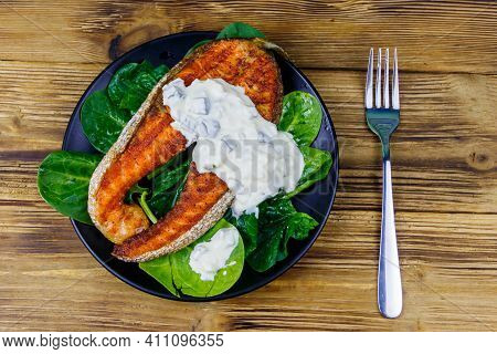 Grilled Salmon Steak With Spinach And Tartare Sauce On Wooden Table. Top View