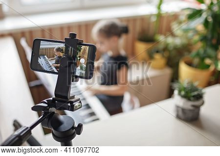 Pretty Young Musician In Classic Black Dress Playing Digital Piano At Home During Online Concert And