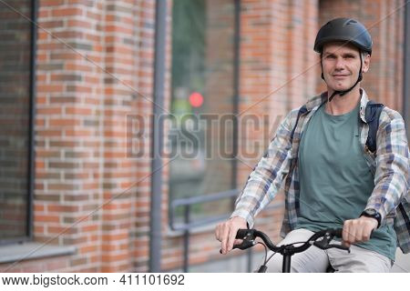 Mature fashionable Caucasian man in tartan shirt and beige trousers  a bicycle helmet on his bike in a city