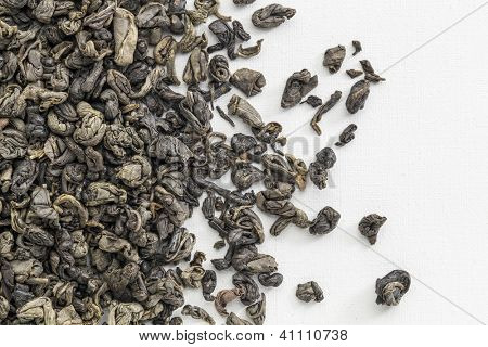background texture of loose leaf Chinese gunpowder (pearl) green tea spilled over white artist canvas