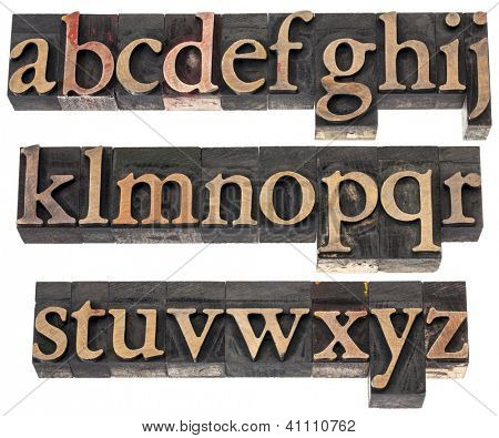 wood type alphabet in letterpress printing blocks stained by color inks, three rows isolated on white