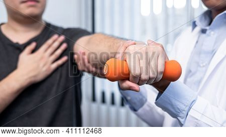 Young Asian Physiotherapist Helping Male Patient Stretching Arm During Exercise Correct With Dumbbel