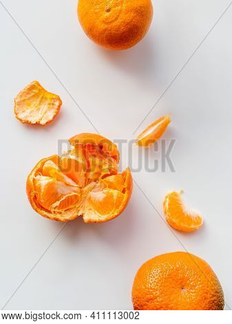 Top View Of Peeled And Whole Tangerine. Peel And Pieces Of Citrus On White Background. Ripe Bright O