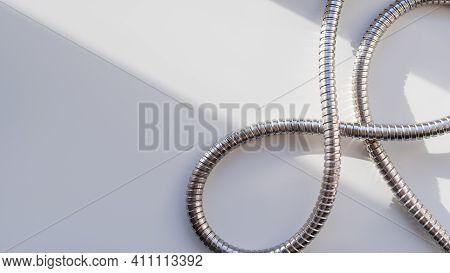 Metal Shower Hose On White Background. Flexible Chrome Tube. Corrugated Plumbing Tube On Geometrical