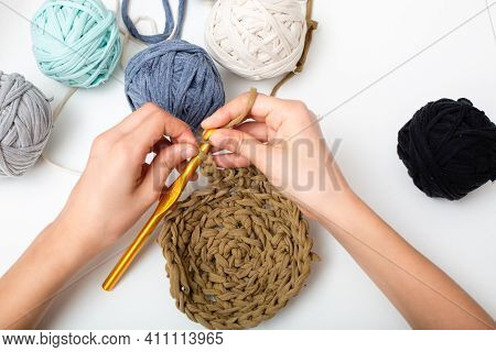 Different Colored Balls Of Yarn. Childrens Hands Are Crocheted And Thread View Frome Above On White