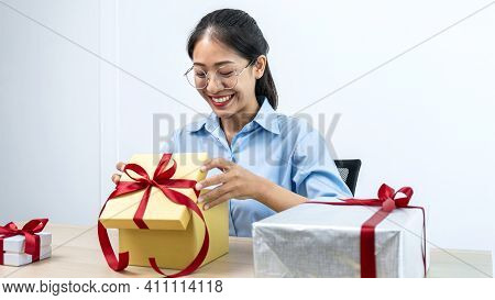 Young Asian Woman Opening A Gift Box With Red Ribbon And Looking Inside Box With Smiling To Enjoy Ce