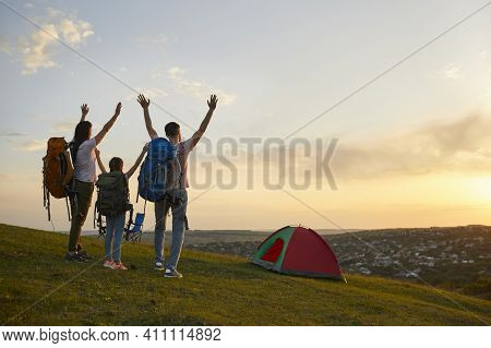 Family Camping In Nature. Parents And Child With Backpacks Enjoying Beautiful Sunset At Campground,