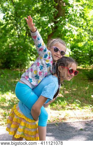 Two Young Sisters Having Fun Together In A Summer Park. Happy Adorable Little Girl On A Piggy Back R