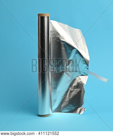 Unwrapped Roll Of Gray Foil On A Blue Background, Close Up