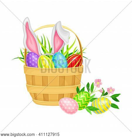 Decorated Easter Eggs Or Paschal Eggs Rested In Wicker Basket With Green Grass And Spring Flowers Ve