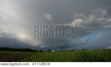Rain Clouds Are A Strip Of Deciduous Forest And Green Grass At The Edge Of A Field And A White Car,