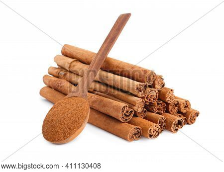 Aromatic Cinnamon Sticks And Spoon With Powder On White Background