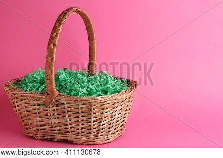 Easter Basket With Green Paper Filler On Pink Background, Space For Text
