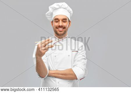 food cooking, asian cuisine and people concept - happy smiling male chef in toque holding something with chopsticks over grey background (focus on chopsticks)