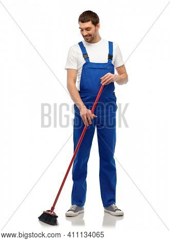 profession, service and people concept - happy smiling male worker or cleaner in overall cleaning floor with broom over white background