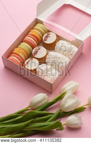 Opened Gift Box Of Desserts: Macarons, Shoux And Zefyrs Isolated On Pink Background With White Tulip