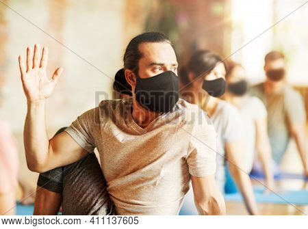 fitness, yoga and healthy lifestyle concept - man wearing face protective black masks for protection from virus disease with group of people doing half lord of the fishes pose in gym or studio