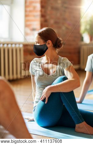 fitness, sport and healthy lifestyle concept - woman with group of people in black masks doing yoga seated spinal twist pose in gym or studio