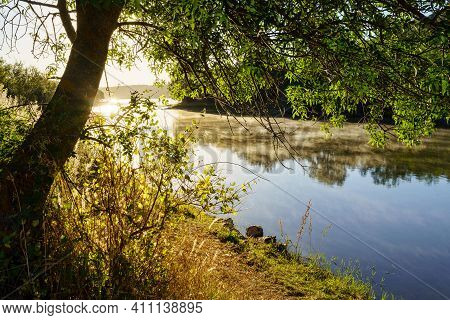Landscape At Sunrise On A Lake With Sun Flares Rising From The Horizon, Reflections In The Water And