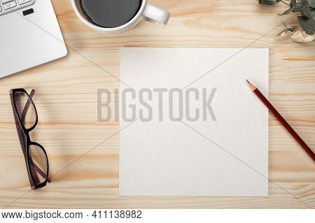 Top View Paper Card On Office Desk Mockup. Blank Paper On Wooden Desk Background. Desk With Blank Pa